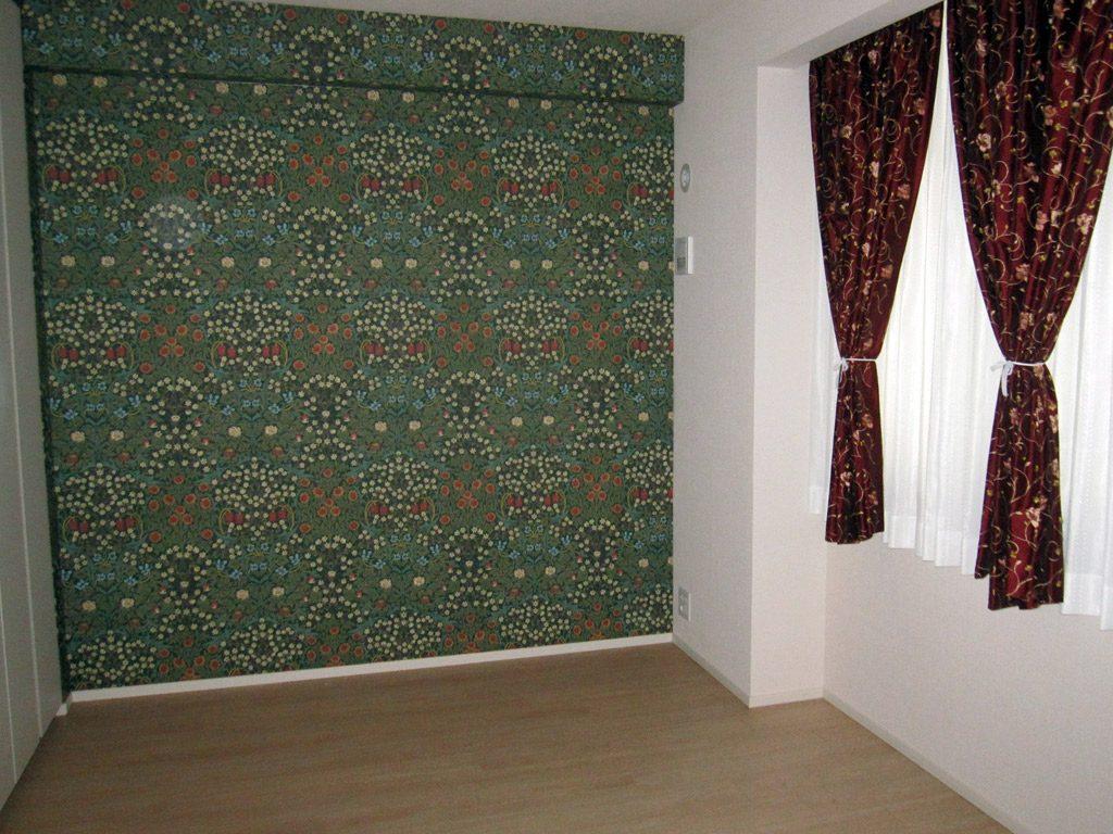窓側はホワイト系のクロスで開放感をだしてアクセントにレッドのカーテンを。