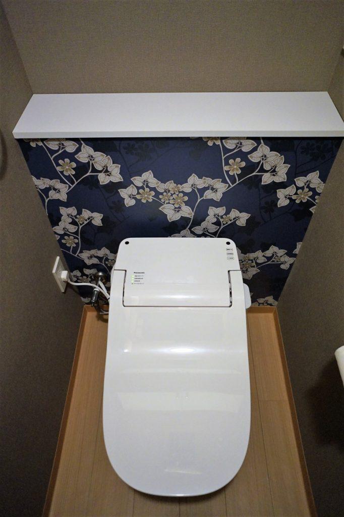トイレの配水管の部分を隠し飾り棚にし、お気に入りの小物を飾ります。収納庫は天井上に。