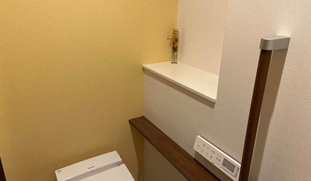 ポップな黄色のアクセントクロスのトイレの写真