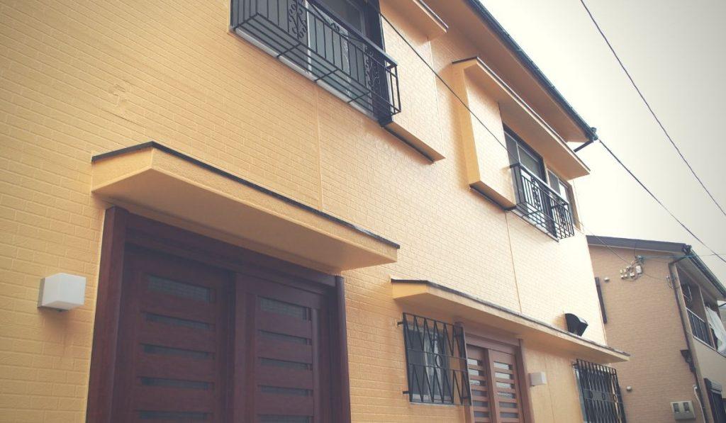 黄色い外壁の二世帯住宅の写真